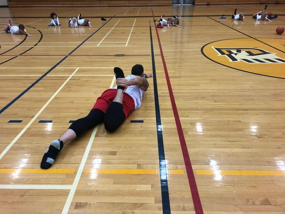 Des jeunes s'entraînent à jouer au basket sur un terrain.