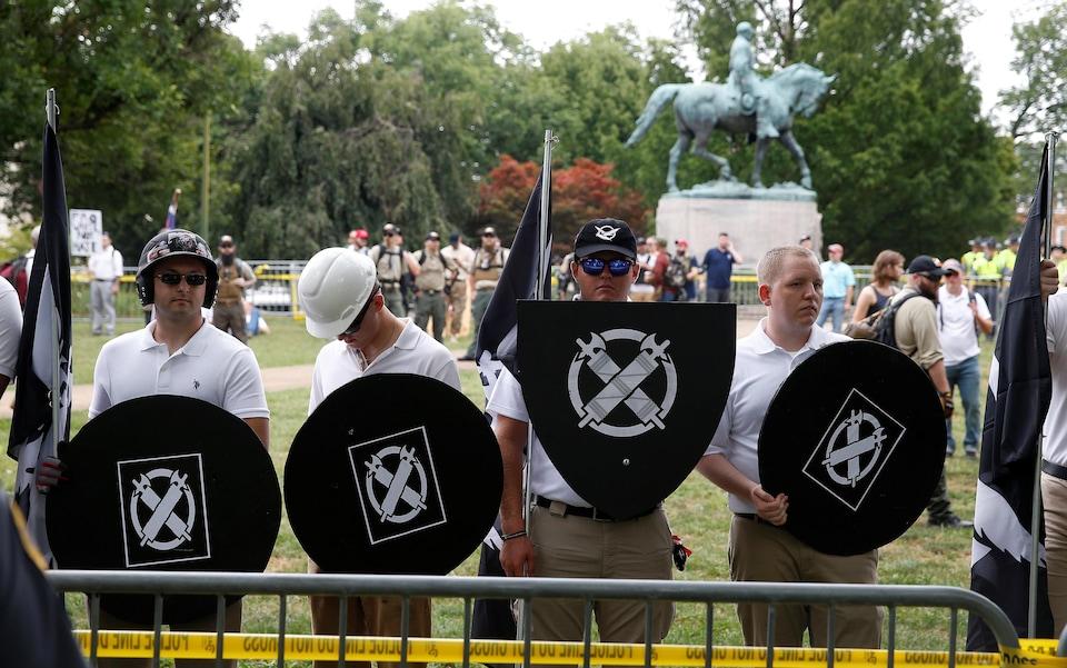 Quatre hommes habillés en blanc tiennent des boucliers noirs à l'insigne de Vanguard America.