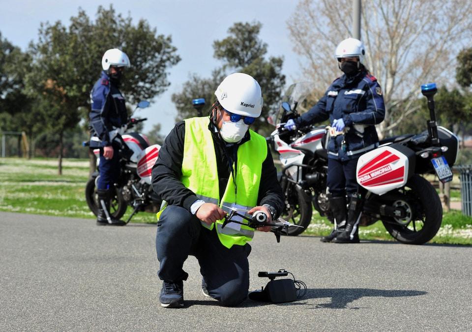 Un policier agenouillé tient un drone devant deux policiers derrière avec leurs motocyclettes.