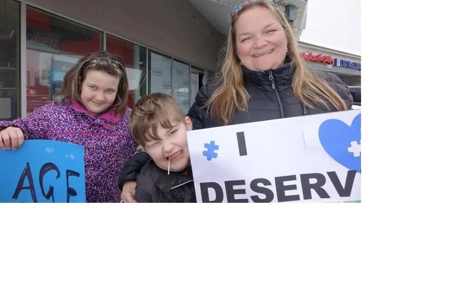 Une femme accompagnée de deux enfants, un garçon et une fille. La femme tient une pancarte ainsi que la fille.