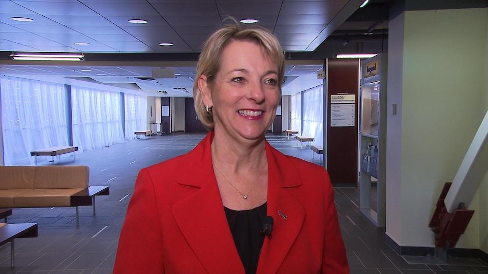 Sylvie Parent, tout sourire, portant un veston rouge.