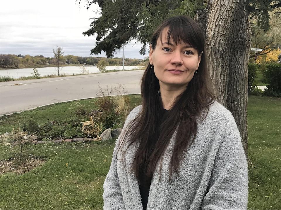 Une femme, Sylvie Schmitt, est prise en photo à l'extérieur, avec la rivière en arrière-plan.