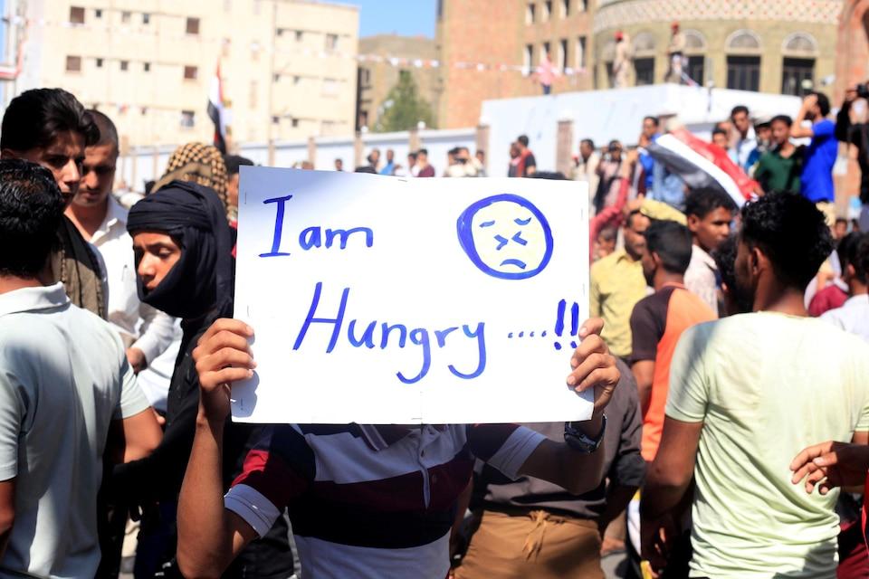 Un manifestant tient une affiche sur laquelle est écrit : «I am hungry».