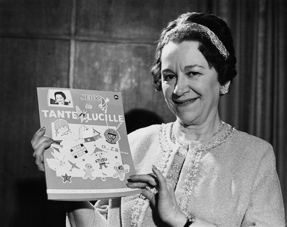 Lucille Desparois montre l'un de ses livres-jeux qu'elle tient dans ses mains.