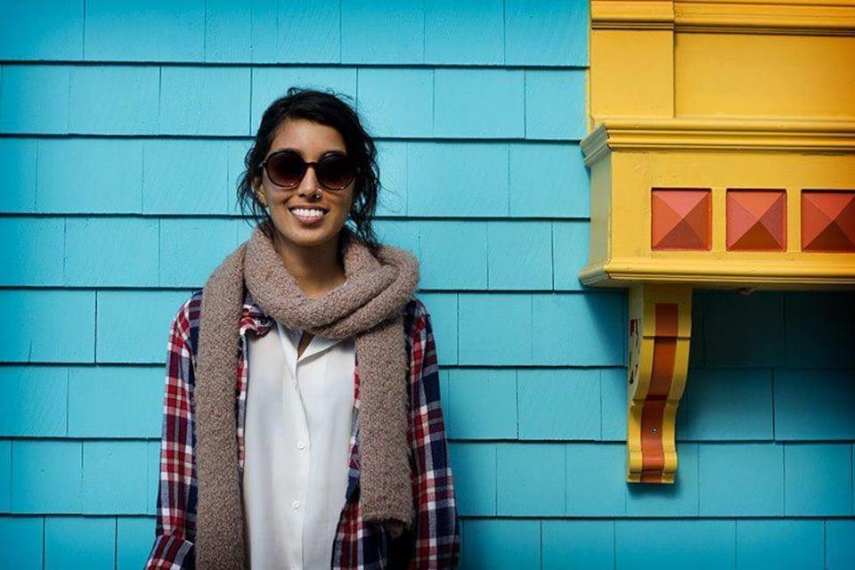 Une jeune femme souriante portant des lunettes fumées pose devant un mur coloré en bleu jade et jaune.