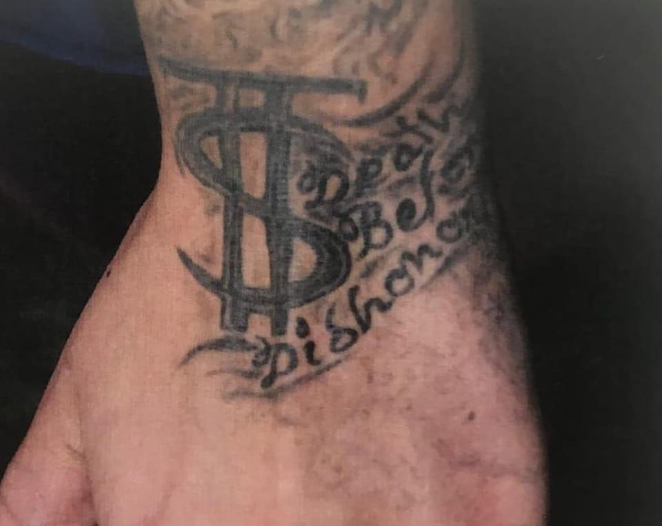 Gros plan sur le dessus d'un poignet gauche sur lequel sont tatouées les lettres «TS» qui débutent un bandeau où l'on peut lire les mots superposés «death», «before» et «dishonor».