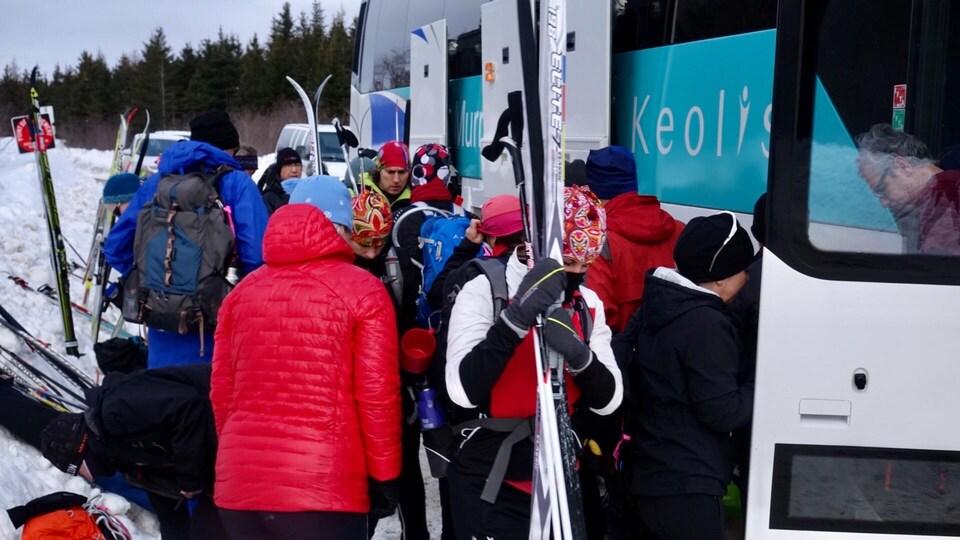 Des skieurs qui récupèrent leurs bagages dans la soute d'un autobus