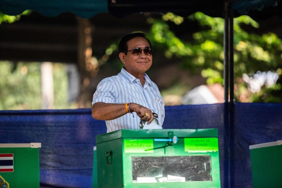 Une homme portant des lunettes fumées sourit à la caméra alors qu'il dépose son bulletin de vote dans l'urne.