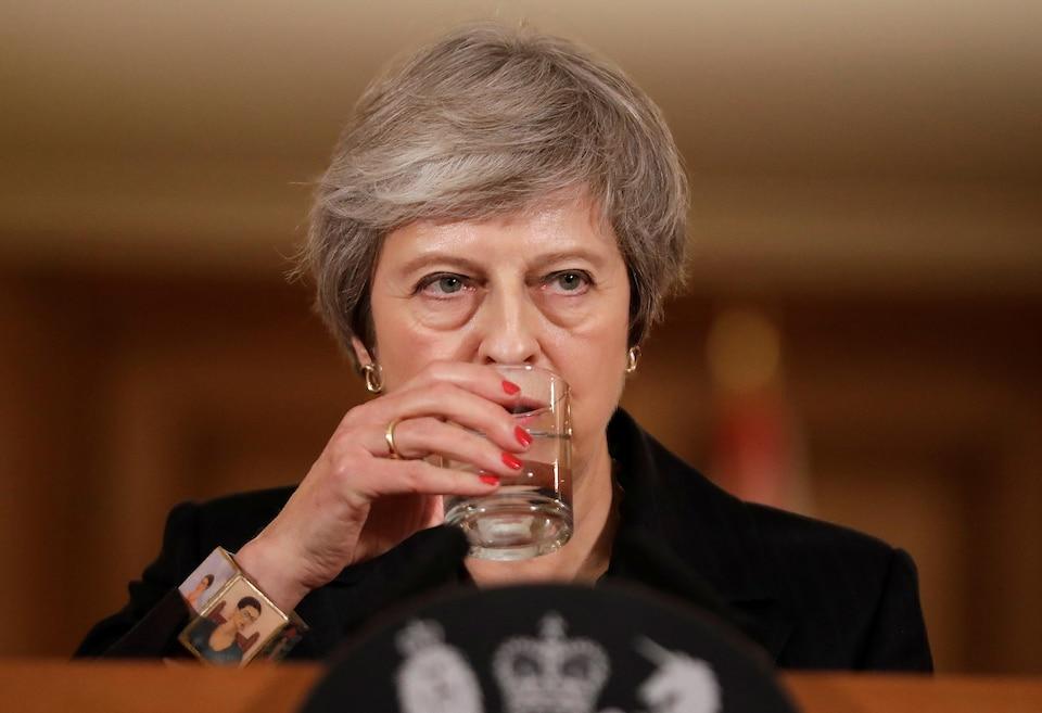 En conférence de presse, la première ministre du Royaume-Uni, Theresa May, boit un verre d'eau en écoutant une question.