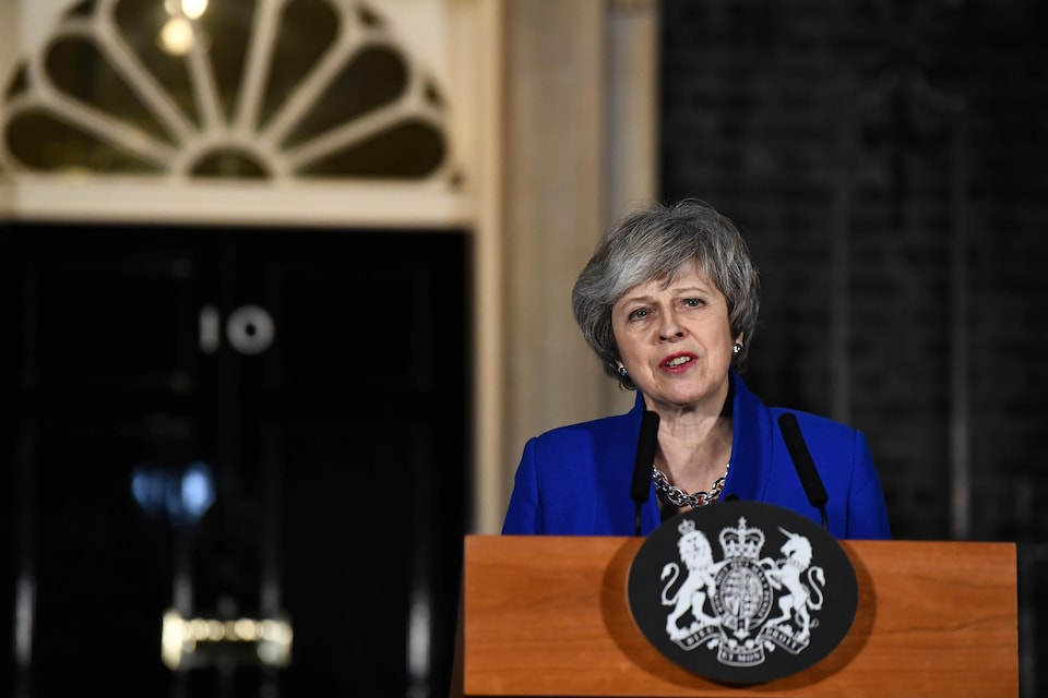 Theresa May, devant des micros, s'adressant aux Britanniques au cours d'une allocution prononcée de l'extérieur de sa résidence de Downing Street.