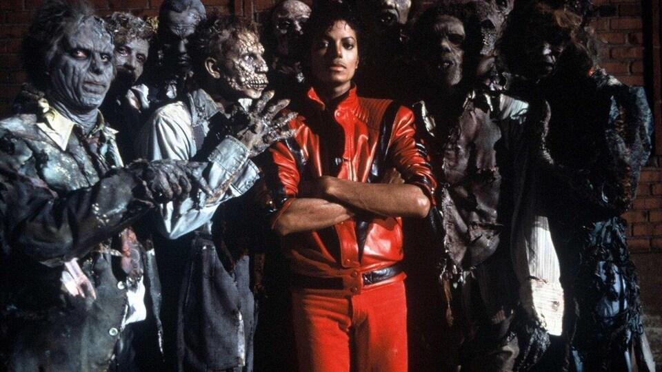 Des zombies entourent le chanteur Michael Jackson lors du tournage de la vidéo pour Thriller.