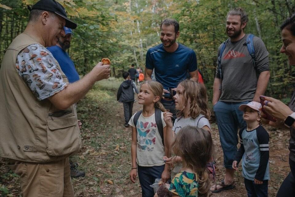 Des enfants regardent un homme qui tient un champignon.