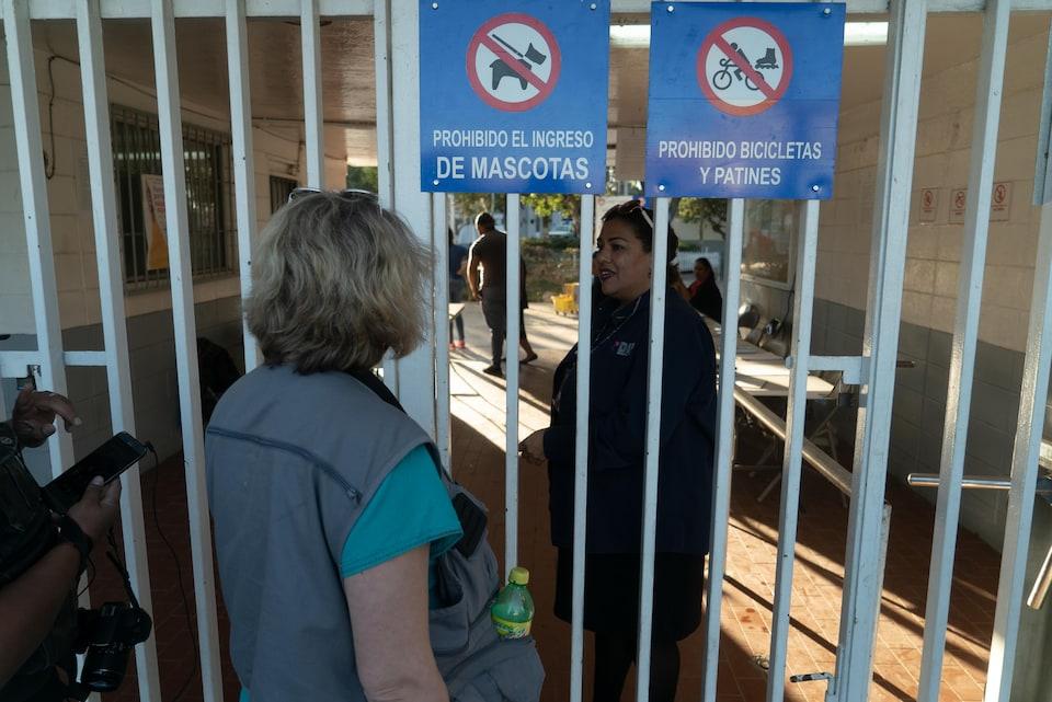 Deux femmes parlent devant un portail d'un stade de Tijuana.