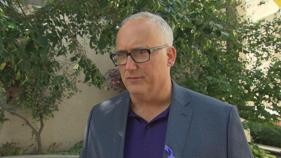 Un homme à lunettes portant une vesteé