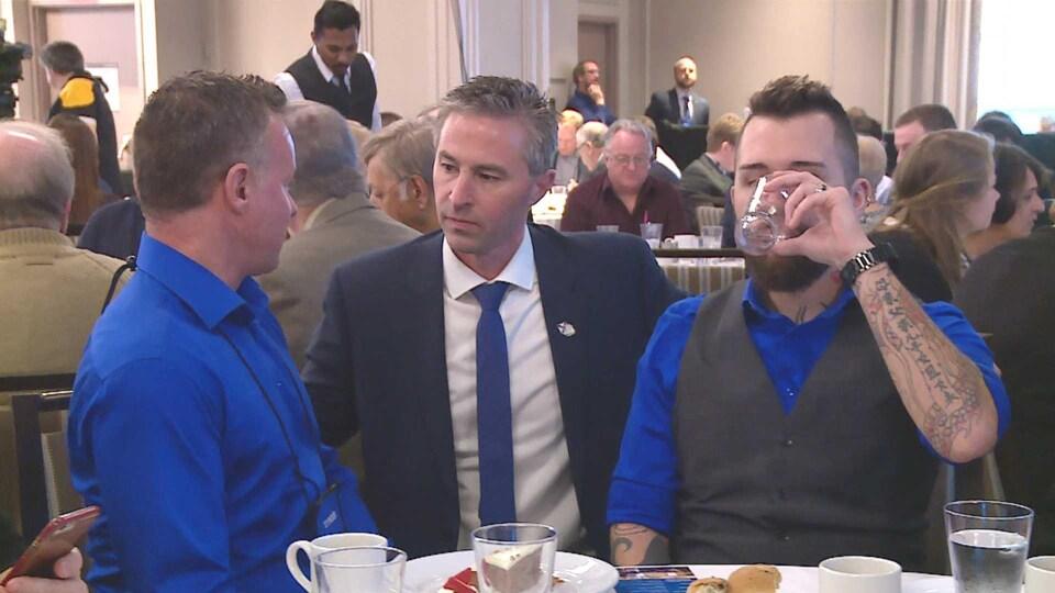 Tim Houston discute avec deux électeurs.