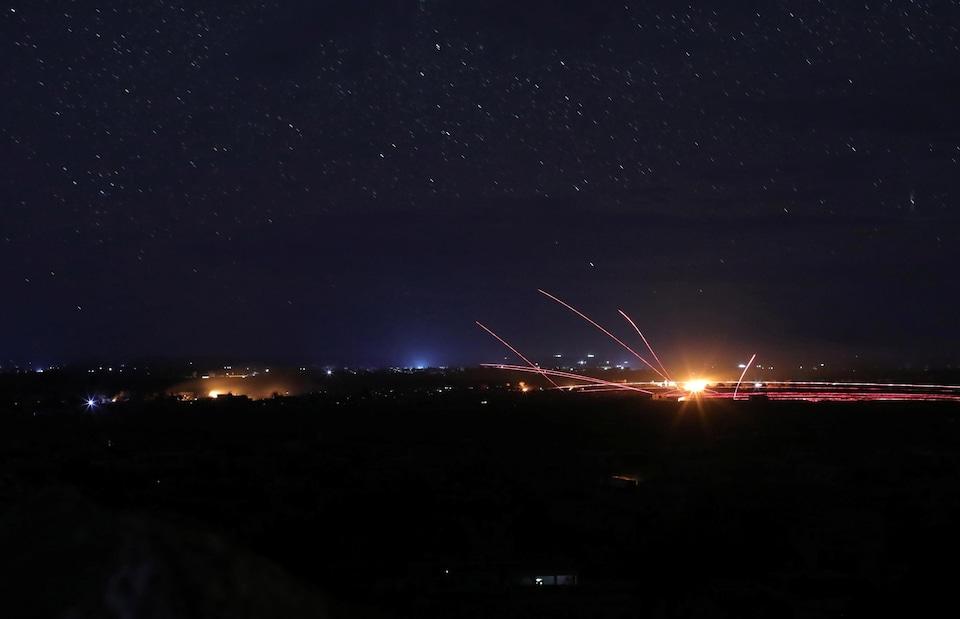 Alors qu'il fait nuit, des missiles sont tirés dans les airs et laissent une traînée de lumière.