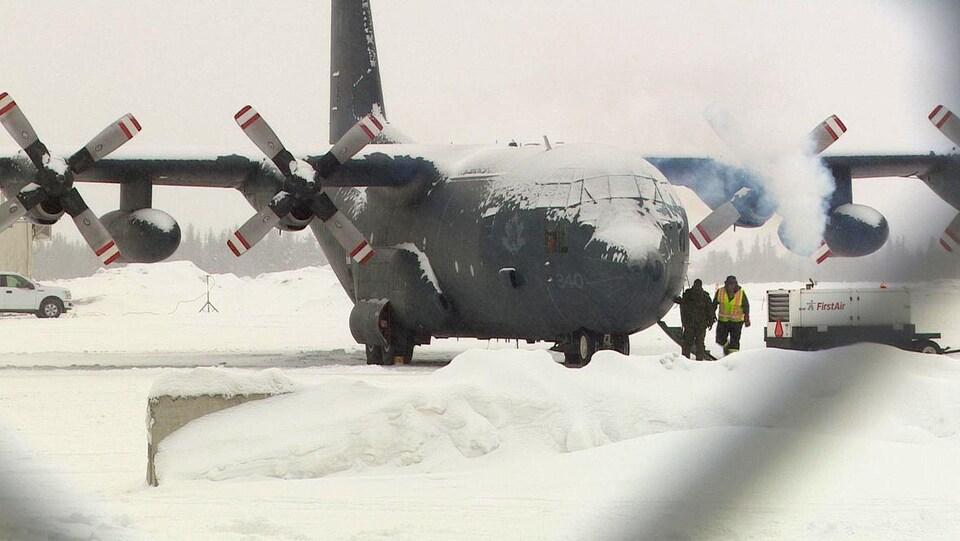 Un avion recouvert de neige avec deux personnes devant.