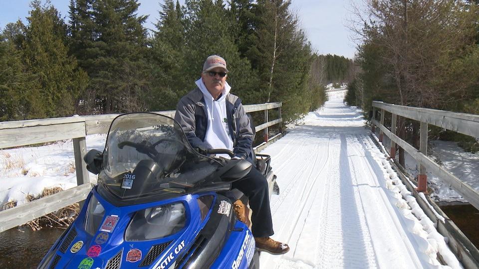 Tony Godin est assis sur sa motoneige sur un pont du sentier.