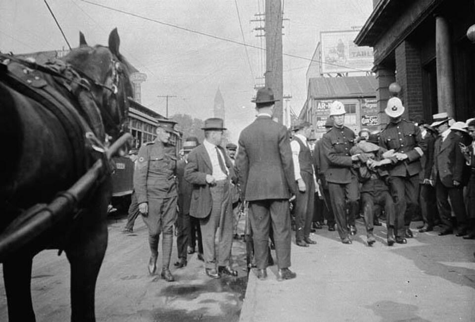 Des policiers traînent un homme tandis que des badauds regardent. On aperçoit un tramway et un cheval.