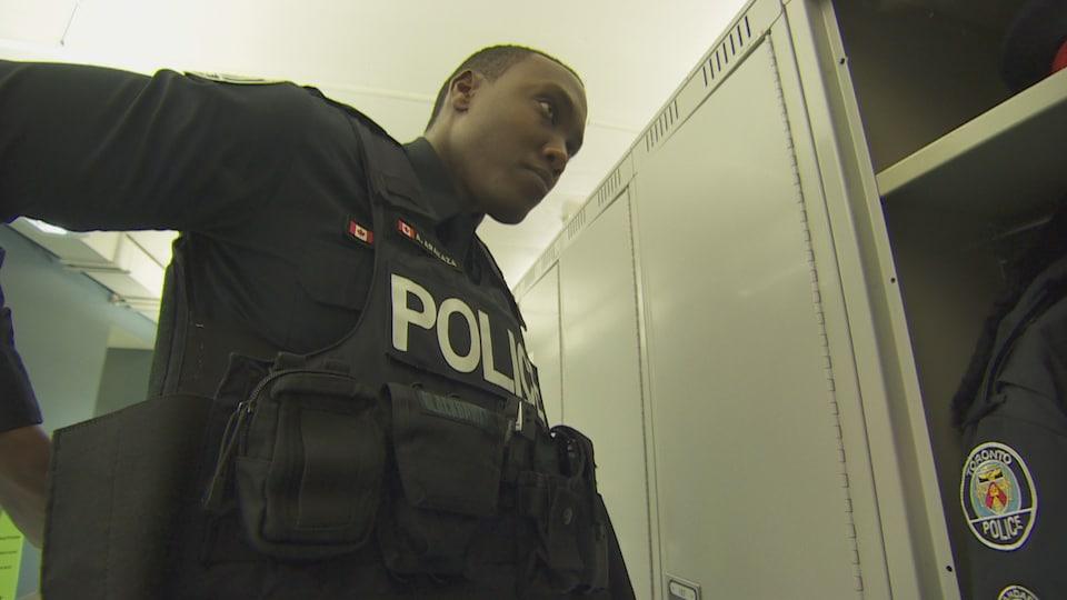 Un homme met son uniforme d'agent de la police de Toronto.