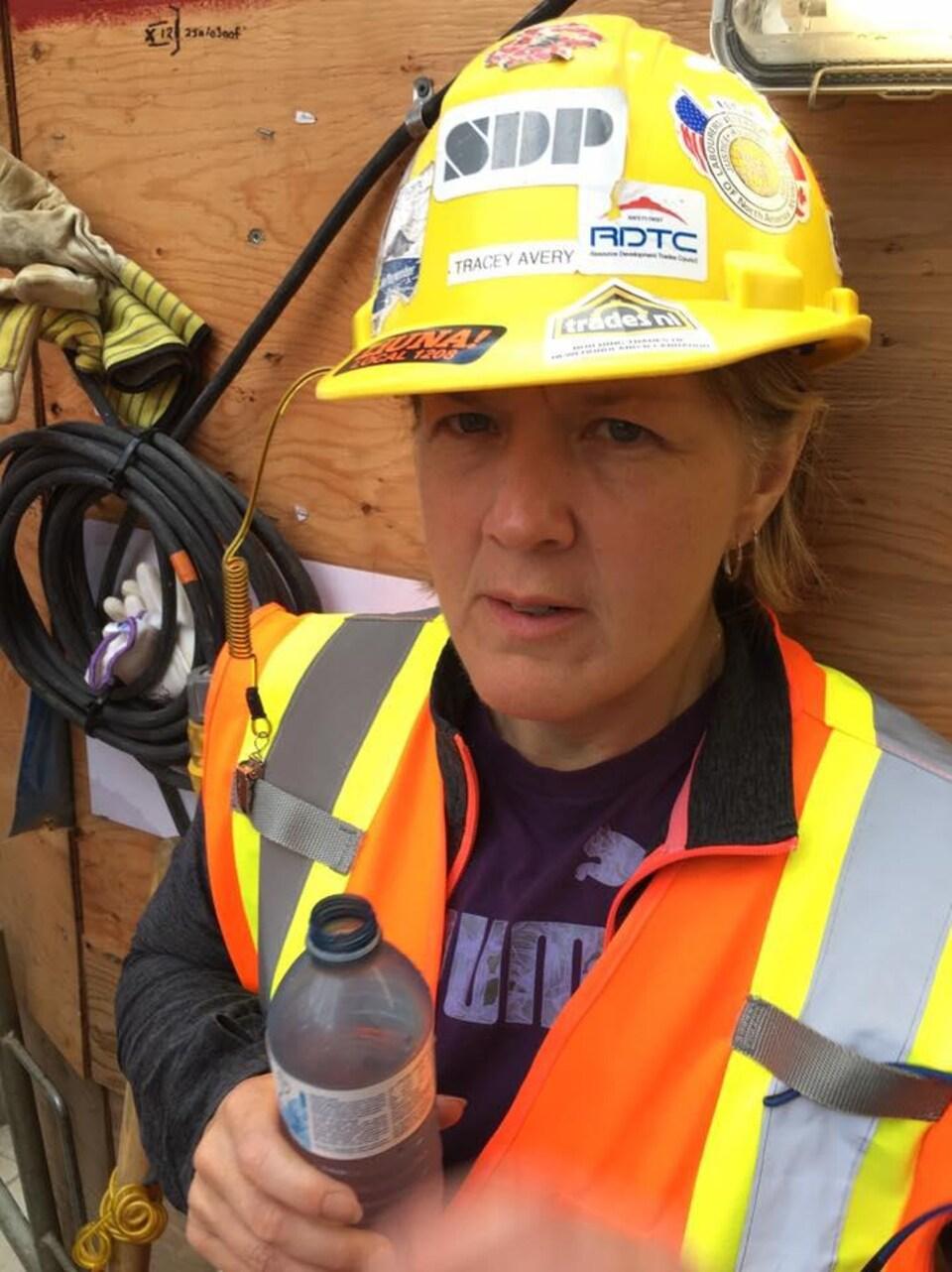 Une femme vêtue d'une veste orange et coiffée d'un casque de construction.