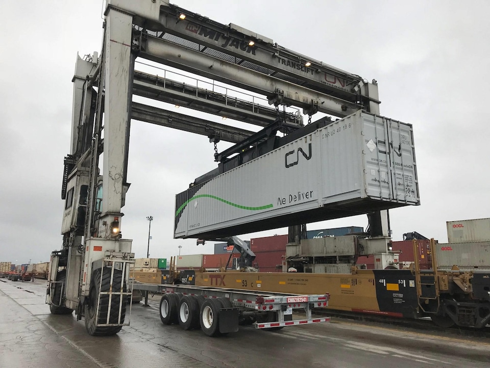 Un conteneur ferroviaire en cours de transfert sur un semi-remorque.