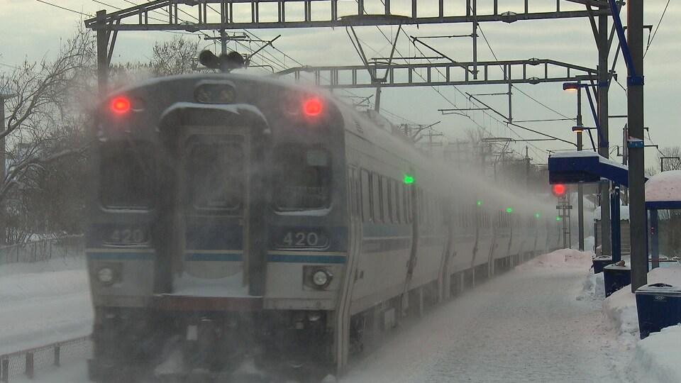 Un train voyage sous la neige dans la banlieue de Montréal.