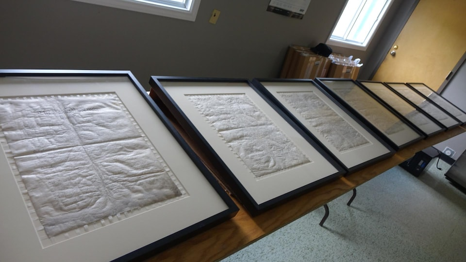Les pages du traité sont encadrées et posées sur des tables.