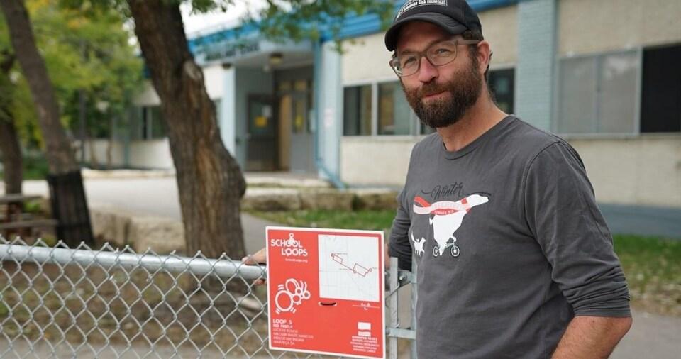 Anders Swanson debout près d'un des panneaux autour de Brooklands School.