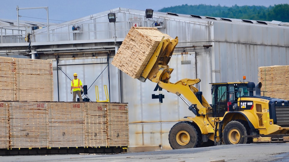 Un chariot élévateur soulève du bois d'oeuvre à l'extérieur de l'usine