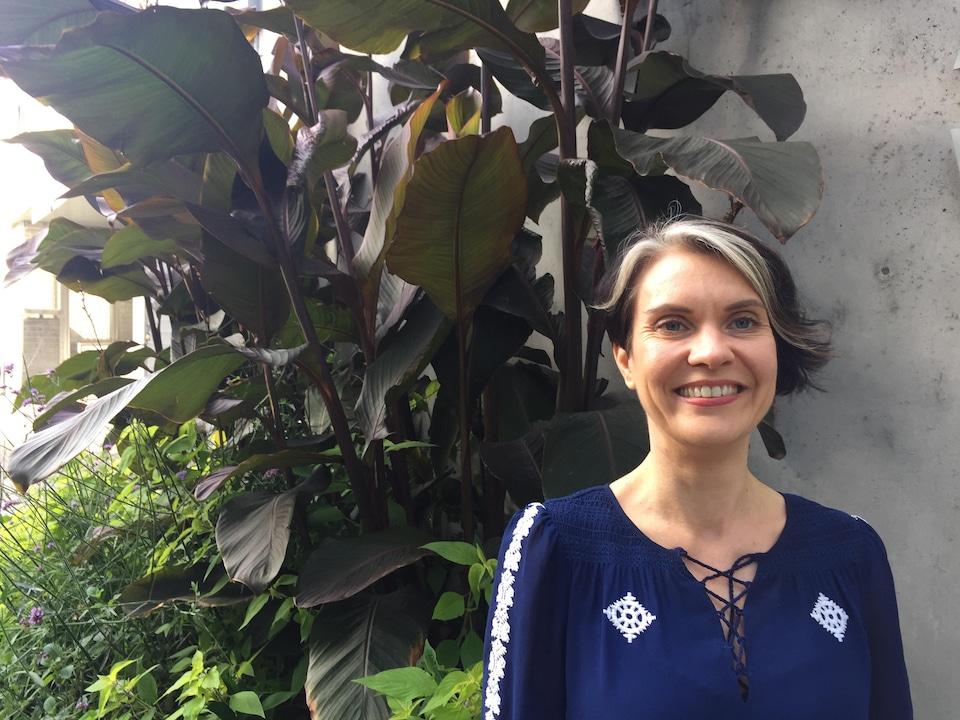 La coordinatrice du Réseau immigration francophone sourit à la caméra, devant un joli bosquet de plantes tropicales.