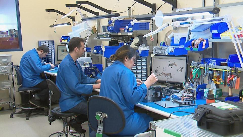 Des employés de l'entreprise Telops assis à leur bureau travaillent avec des composantes électroniques