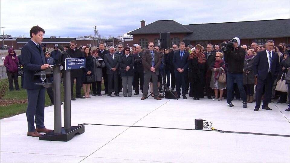 Justin Trudeau devant un lutrin avec en arrière-plan des élus et des citoyens de Lac-Mégantic.