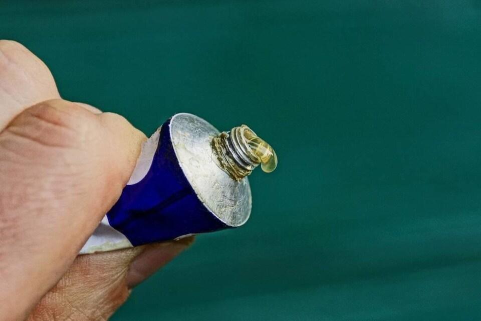 Un tube d'onguent métallisé entre deux doigts.