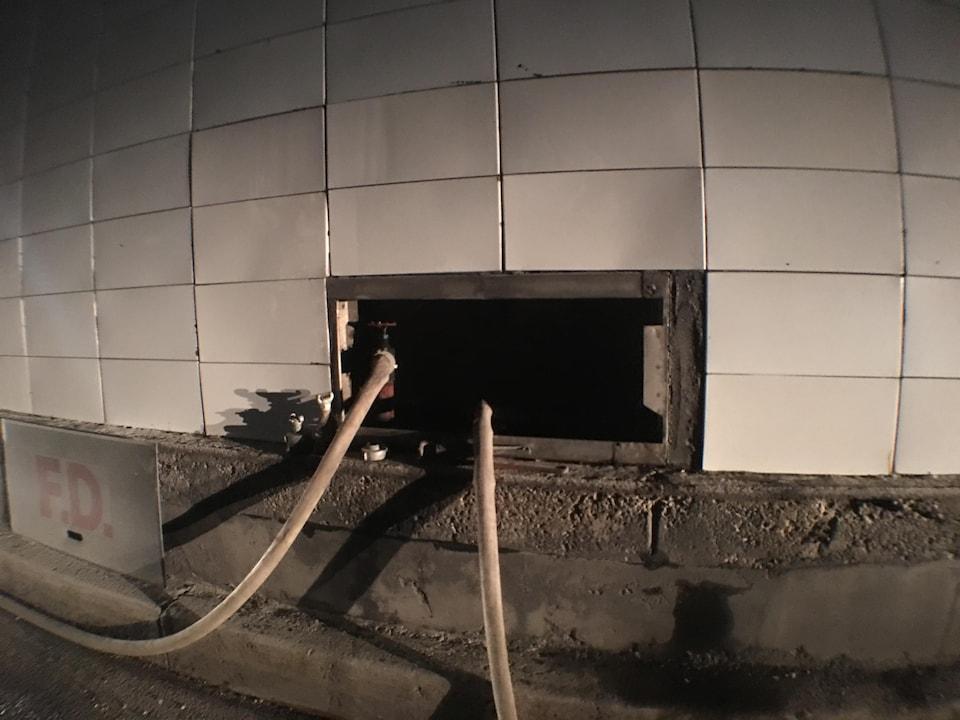On voit deux boyaux branchés dans le mur du tunnel.
