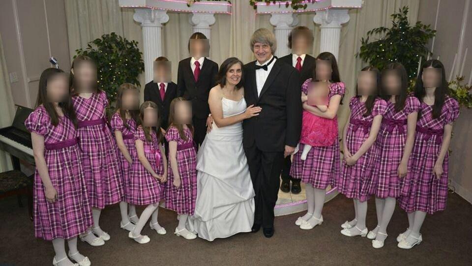 La famille Turpin pose, les filles sont habillées en robe à carreaux et les garçons en habit.
