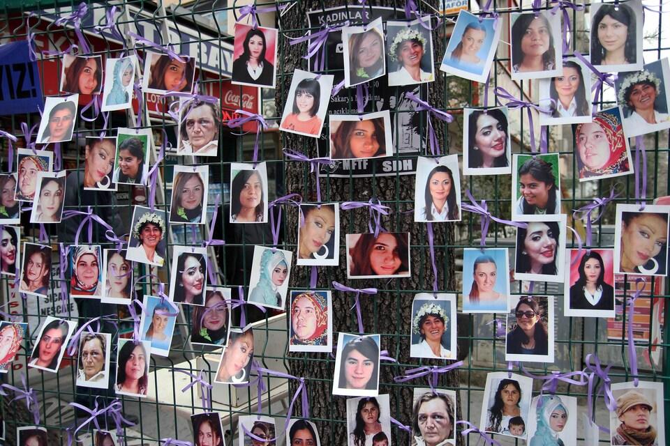 Les photos d'une cinquantaine de femmes sont accrochés à un grillage avec des fils violets