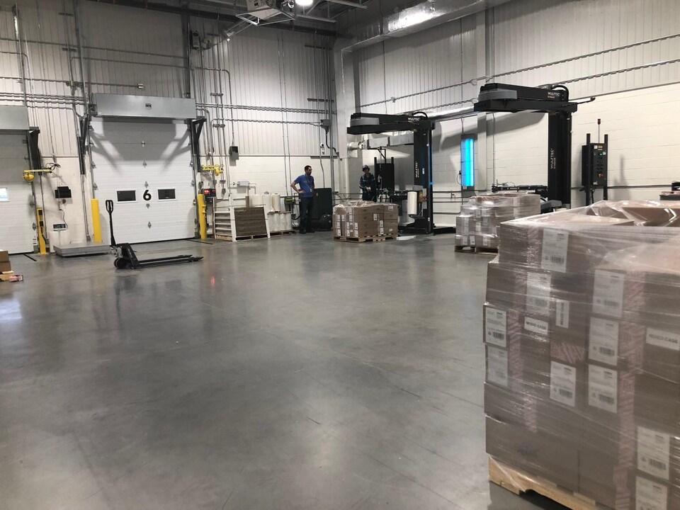 Des machines entourent des piles de boîtes, sous la supervision de deux employés.