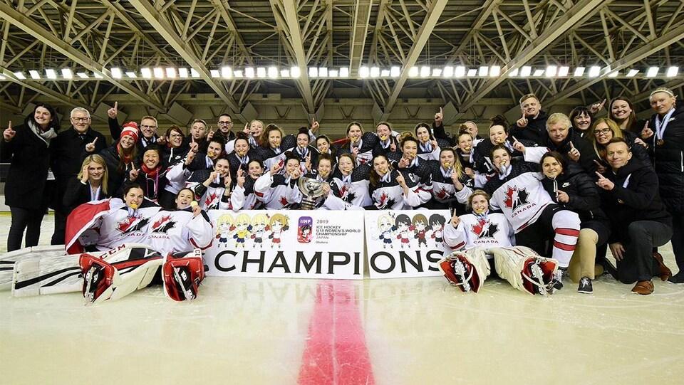 Une équipe de hockey féminine pose le doigt en l'air pour célébrer la victoire de l'équipe.
