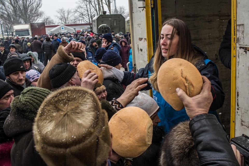 Des travailleurs de l'ONU distribuent du pain aux résidents d'Avdiïvka.