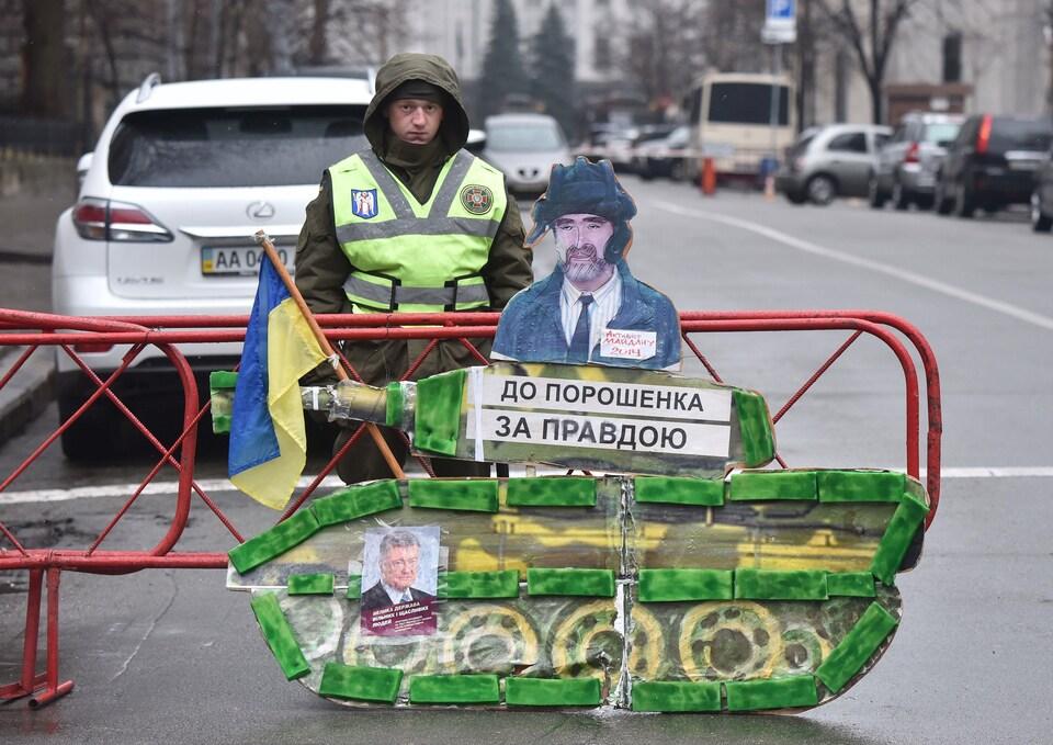 Un policier se tient devant une pancarte en forme de char d'assaut.