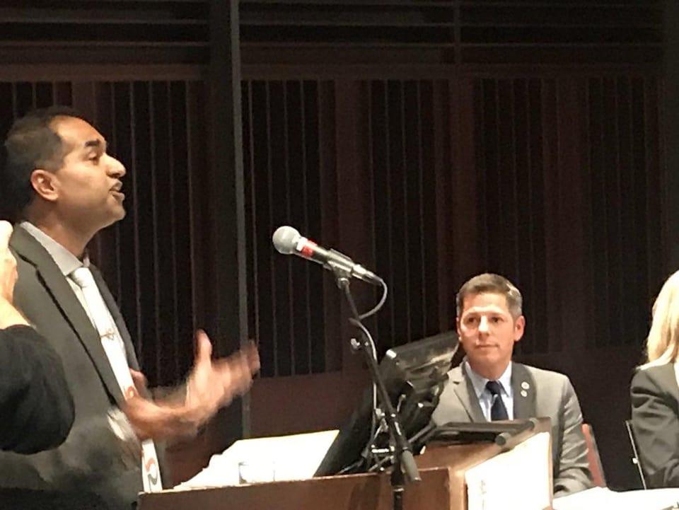 Un homme debout devant un podium gesticule.