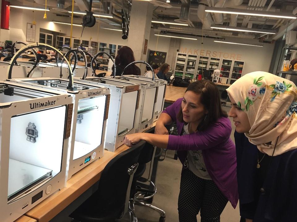 Deux femmes montrent des imprimantes 3D.