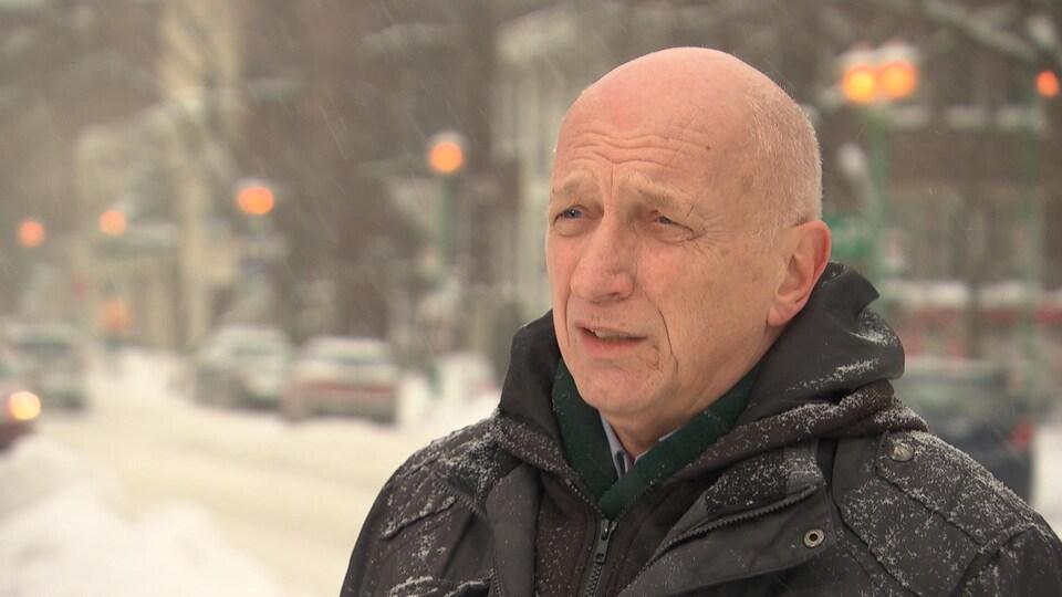 Un homme portant un manteau noir discute avec une journaliste lors d'une entrevue sous la neige.