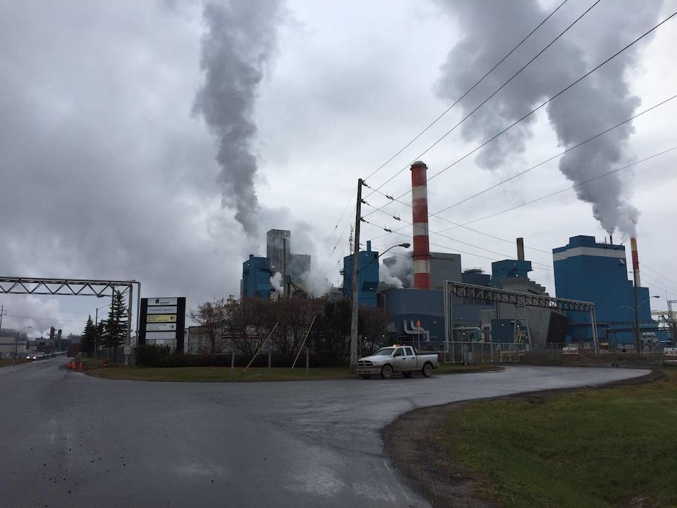 Une usine avec de la fumée sortant de plusieurs cheminées.