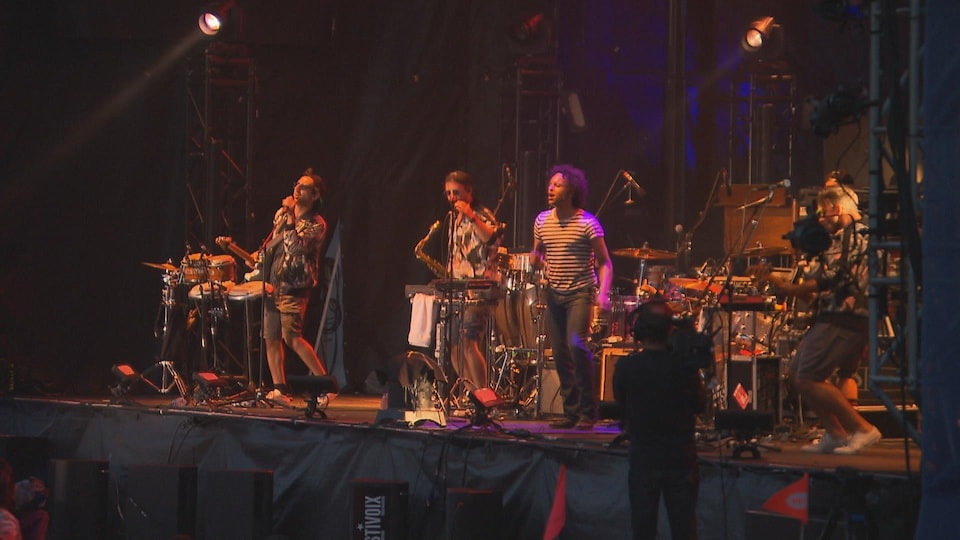 Des jeunes hommes interprètent une pièce sur scène.