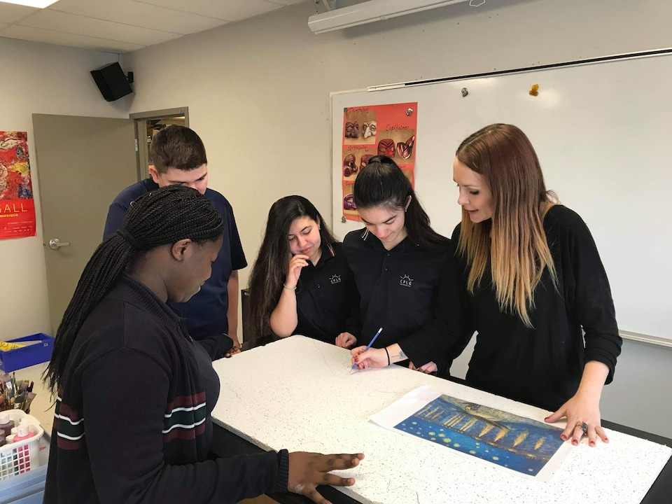 Valérie Tremblay et des élèves penchés sur une table à dessin.