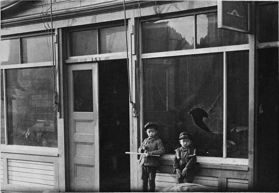 Deux enfants aux traits asiatiques devant une vitrine fracassée