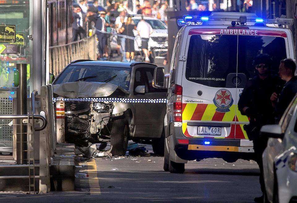 Des policiers australiens se tiennent près d'un véhicule accidenté après avoir arrêté le conducteur qui aurait foncé délibérément sur des piétons à une intersection de Melbourne, le 21 décembre 2017.