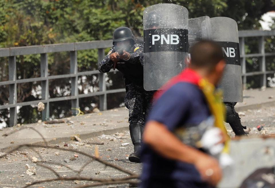 Un officier de la police nationale tire des balles en caoutchouc lors d'une manifestation contre le gouvernement du président vénézuélien Nicolas Maduro à Caracas au Venezuela, le 23 janvier 2019.